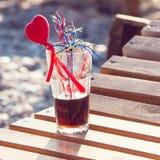 Закройте вверх стекла спиртного коктеиля стоя в песке на тропическом пляже Стоковая Фотография RF