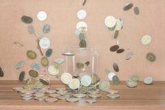 Закройте вверх стеклянной бутылки штабелируя падать серебряных монет Стоковая Фотография RF
