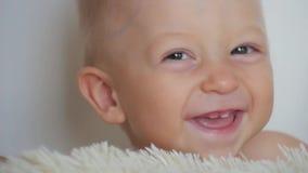 Закройте вверх стороны ` s младенца пока она усмехается и смеется над Милый маленький младенец смотрит в камеру сток-видео
