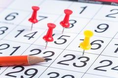 Закройте вверх страницы календаря с Pushpins и карандашем Стоковые Фотографии RF