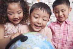Закройте вверх студентов смотря глобус Стоковая Фотография