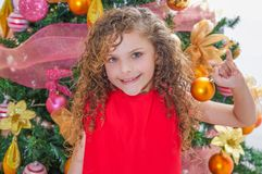 Закройте вверх счастливой девушки, носящ красную блузку и держащ шарик рождества перед рождественской елкой, рождество Стоковые Изображения RF