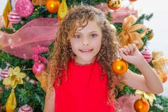 Закройте вверх счастливой девушки, носящ красную блузку и держащ шарик рождества перед рождественской елкой, рождество Стоковое Изображение RF