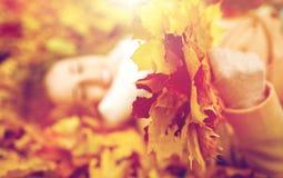 Закройте вверх счастливой женщины лежа на листьях осени Стоковая Фотография