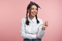 Закройте вверх счастливой женщины с яркой улыбкой на стороне, нося белой рубашке и держателе, изолированных над розовым фоном стоковое фото