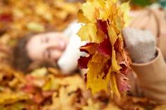 Закройте вверх счастливой женщины лежа на листьях осени Стоковое Фото