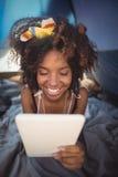 Закройте вверх счастливой женщины используя цифровую таблетку пока лежащ вниз в шатре Стоковое фото RF