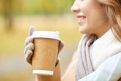 Закройте вверх счастливой женщины с кофе в парке осени Стоковое Изображение