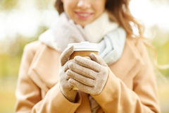 Закройте вверх счастливой женщины с кофе в парке осени Стоковое Фото