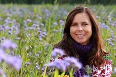 Закройте вверх счастливой зрелой женщины в поле цветка стоковые изображения