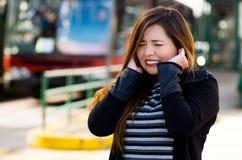 Закройте вверх счастливой красивой молодой женщины покрывая ее уши с обеими руками на улице в городе с звуком Стоковое Изображение
