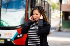 Закройте вверх счастливой красивой молодой женщины покрывая ее уши с обеими руками на улице в городе с звуком Стоковая Фотография RF