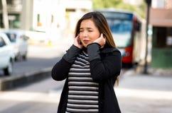 Закройте вверх счастливой красивой молодой женщины покрывая ее уши с обеими руками на улице в городе с звуком Стоковые Изображения