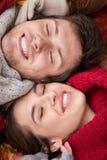 Закройте вверх счастливых пар лежа на листьях осени Стоковые Изображения