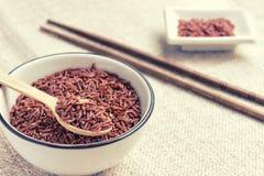 Закройте вверх сырцового краснокоричневого риса на деревянной ложке в белом cera Стоковое фото RF