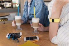 Закройте вверх телефоны на таблице пока девушки держа их пить Стоковое Изображение