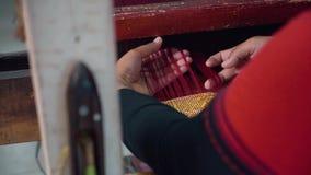 Закройте вверх ткани индонезийских рук женщины сплетя с машиной тени ног-treadle акции видеоматериалы