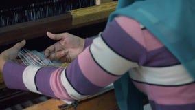 Закройте вверх ткани индонезийской женщины сплетя с машиной тени ног-treadle сток-видео