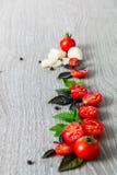 Закройте вверх томатов вишни, чеснока и свежего базилика на серой деревянной предпосылке Рамка скопируйте космос Стоковые Изображения RF