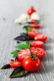 Закройте вверх томатов вишни, чеснока и свежего базилика на серой деревянной предпосылке Рамка скопируйте космос Стоковое фото RF