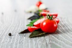 Закройте вверх томатов вишни, чеснока и свежего базилика на серой деревянной предпосылке Рамка скопируйте космос Стоковое Изображение