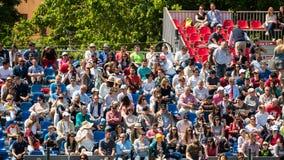 Закройте вверх толпы людей поддерживая их любимого игрока во время спички тенниса Стоковая Фотография