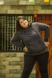 Закройте вверх тучной женщины делая тренировку йоги на outdoors, в запачканной предпосылке Стоковые Фото