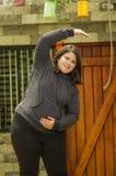 Закройте вверх тучной женщины делая тренировку йоги на outdoors, в запачканной предпосылке Стоковые Изображения