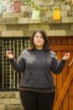 Закройте вверх тучной концентрируя женщины делая тренировку йоги на outdoors, при оба оружия протягивая, в запачканной предпосылк Стоковые Изображения