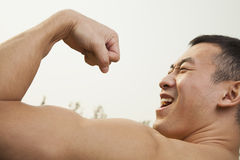 Закройте вверх уверенно, мышечного, молодого человека показывая и изгибая его бицепс Стоковое фото RF