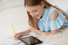 Закройте вверх умной девушки делая домашнюю работу дома Стоковое Изображение