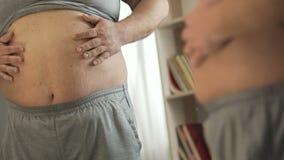 Закройте вверх унылого толстенького человека стоя перед зеркалом и касающим тучным животом сток-видео
