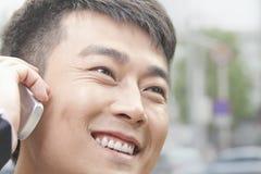 Закройте вверх усмехаясь бизнесмена на телефоне в Пекине Стоковое фото RF