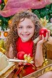 Закройте вверх усмехаясь девушки нося красную блузку и держа шарик рождества и подарка в каждом руки, с рождественской елкой Стоковое Изображение RF