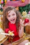 Закройте вверх усмехаясь девушки нося красную блузку и держа шарик рождества и подарка в каждом руки, с рождественской елкой Стоковые Изображения RF