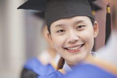 Закройте вверх усмехаясь женского аспиранта стоя в ряд студент-выпускников нося mortarboard Стоковые Изображения