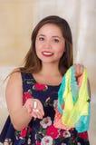 Закройте вверх усмехаясь молодой женщины, держащ сортированное красочное нижнее белье и таблетку мягкого желатина влагалищную или Стоковое Фото