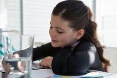 Закройте вверх усмехаясь документа чтения коммерсантки на столе Стоковое фото RF