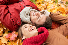 Закройте вверх усмехаясь пар лежа на листьях осени Стоковая Фотография