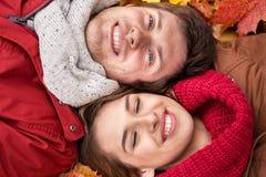 Закройте вверх усмехаясь пар лежа на листьях осени Стоковые Фотографии RF