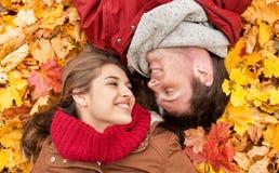 Закройте вверх усмехаясь пар лежа на листьях осени Стоковые Изображения RF