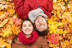 Закройте вверх усмехаясь пар лежа на листьях осени Стоковое фото RF