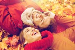 Закройте вверх усмехаясь пар лежа на листьях осени Стоковая Фотография RF