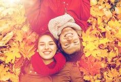 Закройте вверх усмехаясь пар лежа на листьях осени Стоковые Изображения