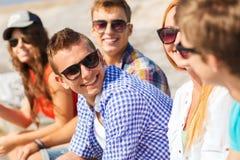 Закройте вверх усмехаясь друзей сидя на улице города Стоковая Фотография RF