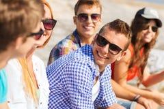 Закройте вверх усмехаясь друзей сидя на улице города Стоковые Фото