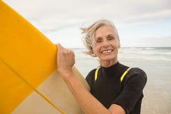 Закройте вверх усмехаясь старшей женщины держа surfboard пока стоящ на береге Стоковые Фото