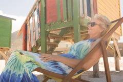 Закройте вверх усмехаясь старшей женщины при солнечные очки отдыхая на стуле Стоковые Фотографии RF