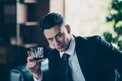 Закройте вверх фото красивое он он его задумчивые обдумывают напиток вискиа оружий рук наслаждаются перерывом перерыва провозглаш стоковые фото