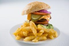 Закройте вверх фраев бургера и француза в плите Стоковое Изображение RF